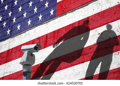 Security camera on the border with painted Usa flag on textured cement wall and people shadows. Concept political relations with neighbors.