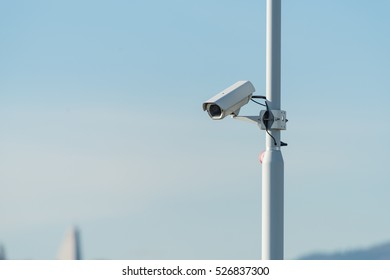Security camera pointing to down on a pole on a blue sky background