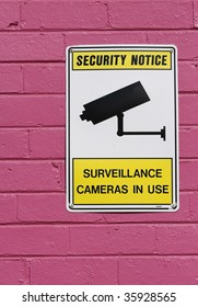 Security camera sign on a bright pink wall