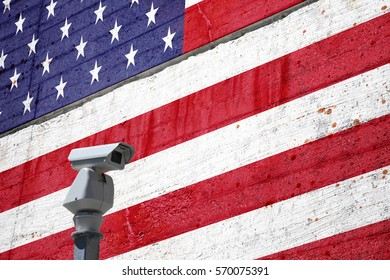Security camera and the textured cement wall with painted Usa flag background. Concept political relations with neighbors.