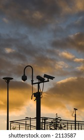 Security cameras silhouetted against an evening sky
