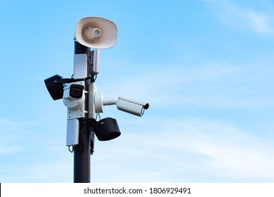 Security cameras and speakers on a pole above a blue sky. Close-up of outdoor surveillance cameras, floodlights and loudspeakers on a street pole. Ensuring security on the street.