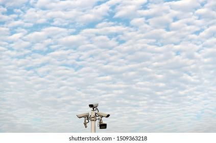Security cameras under cloud sky.