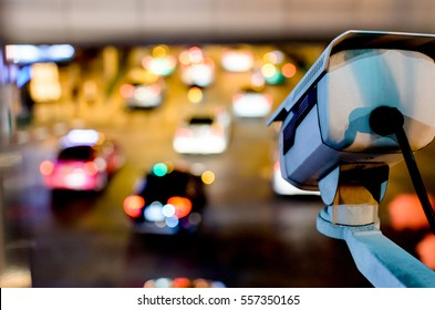 A Security CCTV camera has focus and recording a lot of car on the road with traffic jam at night city in Bangkok Thailand.