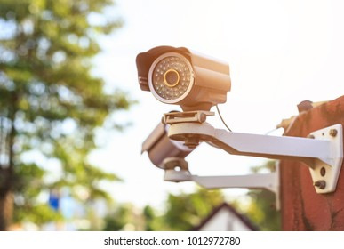 Security CCTV camera installed on wall in front of village at public area on blur green background