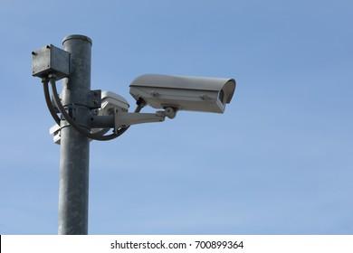 Security CCTV camera on blue sky background