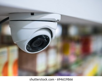 Security CCTV camera or surveillance system in blurred pharmacy background.