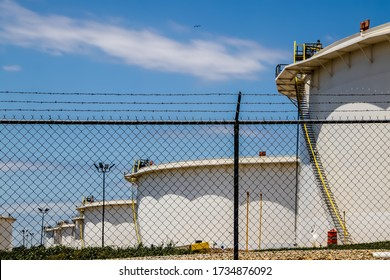 Security chain link fence with rows of barbed wire on top around tank farm with rows of huge oil containers in Cushing OK with an airplane flying above