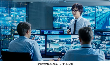 In the Security Control Room Chief Surveillance Officer Briefs Two of His Subordinates. Multiple Screens Show that They Guard Object of Big Importance.