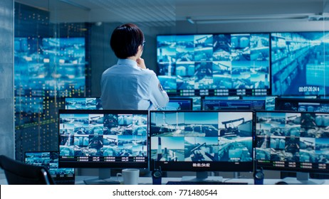 In the Security Control Room Officer Monitors Multiple Screens for Suspicious Activities. He Guards Internationally Important Logistics Facility.