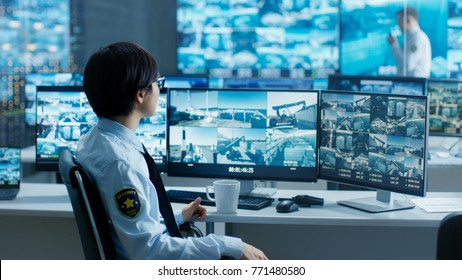 In the Security Control Room Officer Monitors Multiple Screens for Suspicious Activities, He Drinks from a Mug. He's Surrounded by Monitors and Guards Port of National Importance.