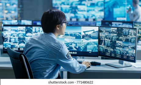 In the Security Control Room Officer Monitors Multiple Screens for Suspicious Activities. He's Surrounded by Monitors and Guards Facility of National Importance.