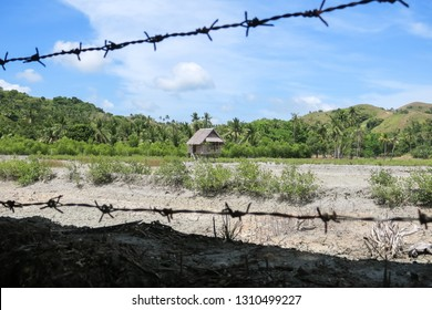Security fence and rustic village hut in hilly Philippine field - Cotabato, Mindanao
