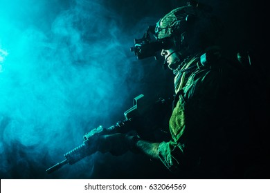 Security forces operator in Combat Uniforms with rifle, in the face of danger. Facing enemy, he is ready to fight. Studio contour silhouette shot, toned and colorized, backlight, profile side view