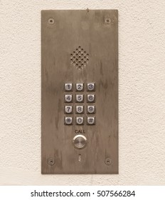 Security. Found on the outside of gated communities, a voice door entry phone with key pad for codes to be entered found on a concrete cream stucco wall.