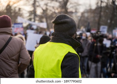 Security guard in bright yellow jacket at a political rally, image taken from his back