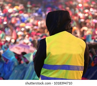 security guard controls people during an important event during a rainstorm with lots of rain