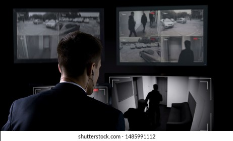 Security guard in earphones watching robbery attempt on surveillance cameras