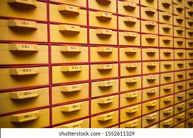 Security guard a large yellow cabinet with cells and numbers for storing personal files and small details. Concept of storing important things or documents