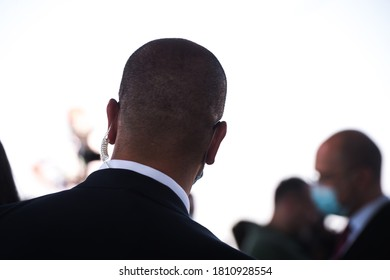 Security guard listening to his earpiece on event. Back of jacket showing. secret service guard. private bodyguard. man with earpiece in crowd. Black suit.