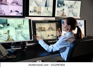 Security guard monitoring modern CCTV cameras in surveillance room
