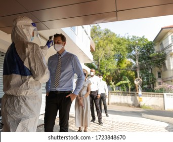 Security guard in PPE suit uses infrared thermometer measuring temperature with European staff scanning for Coronavirus or Covid-19 symptom at office entrance. International medical healthcare system