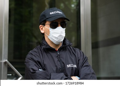 Security Guard Standing In Face Mask At Entrance