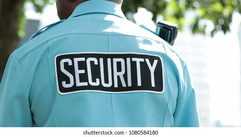 Security guard standing on guard overlooking territory and seeing if everything is safe. Security tag stamped on uniform