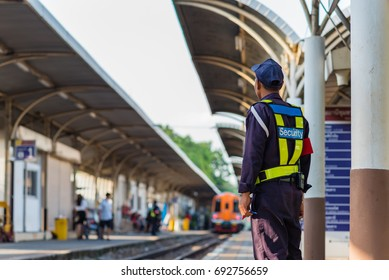 security guard standing wait for train arrived at railway station in Bangkok, Thailand