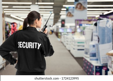 Security guard using portable radio transmitter in shopping mall, space for text - Shutterstock ID 1724123995