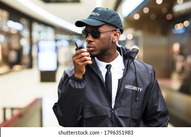 Security Guard Using Walkie Talkie In Shopping Mall