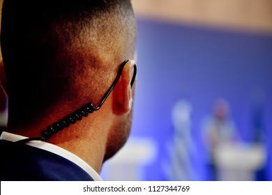 A Security Guard wears an ear headset during a government summit meeting.