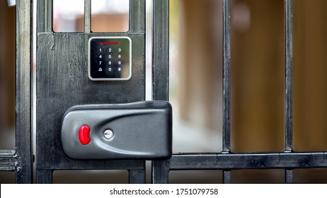 A security lock on black iron gate with a touch panel for access code key or a classic key in the keyhole with a red button for opening, closeup modern security mechanism.