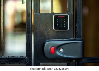 A security lock on an iron gate with a touch panel for access by an access code key or a classic key in the keyhole with a red button for opening.