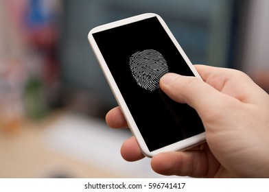 Security - Man's Hand With Smartphone With Fingerprint on Display - Office in Background