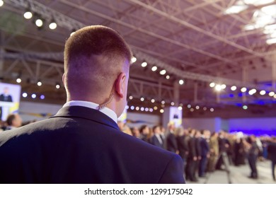 Security on public event. Secret guard service.  Private bodyguard with earpiece standing among crowd. Safety of govern and business meeting. Secret service agent listening to his earpiece, side.