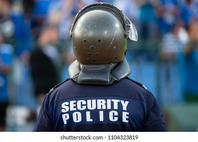 Security police officer with protective helmet seen from his back. Unrecognizable people.