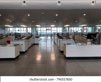 Security screening area inside an airport. Metal detectors and x-ray scanners at security checkpoint inside an airport. Clean and modern airport design. No people. Airport interior.