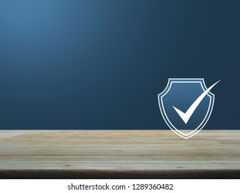 Security shield with check mark flat icon on wooden table over light blue gradient background, Technology internet cyber security and anti virus concept