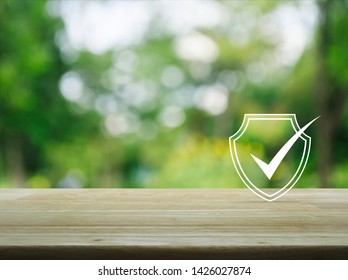Security shield with check mark flat icon on wooden table over blur green tree in park, Technology internet cyber security and anti virus concept