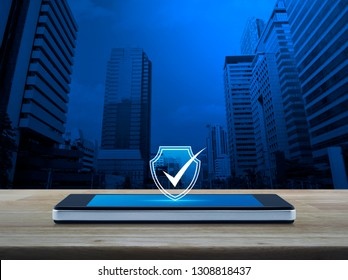 Security shield with check mark icon on modern smart mobile phone screen on wooden table over office city tower and skyscraper, Technology internet cyber security and anti virus concept