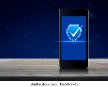 Security shield with check mark icon on modern smart mobile phone screen on wooden table over fantasy night sky and moon, Technology internet cyber security concept