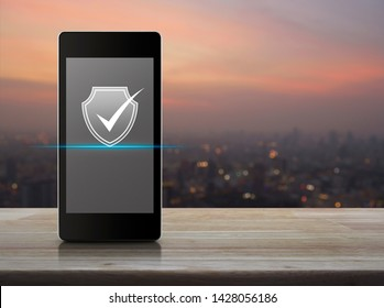 Security shield with check mark icon on modern smart mobile phone screen on wooden table over blur of cityscape on warm light sundown, Technology internet cyber security concept