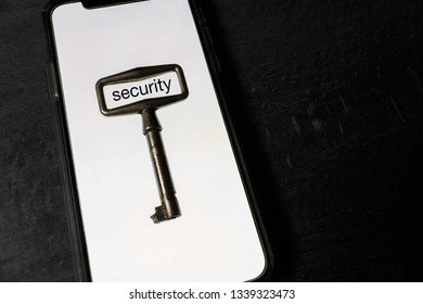 security of the smartphone concept. close-up of the key lies on the white screen of the smartphone as a symbol of smartphone data theft prevention.