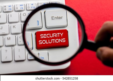 SECURITY SOLUTIONS word written on keyboard view with magnifier glass