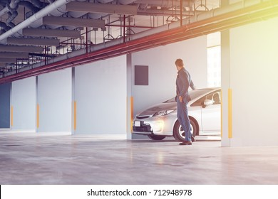 Security system. Full length of a professional confident businessman setting the alarm on his car and standing near his auto in the parking lot