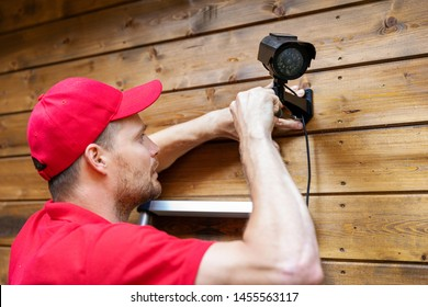 security system technician installing surveillance camera on wooden house wall