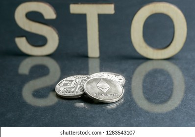 Security Token Offering STO sign with wooden letters and silver coins in front of it, Ethereum concept