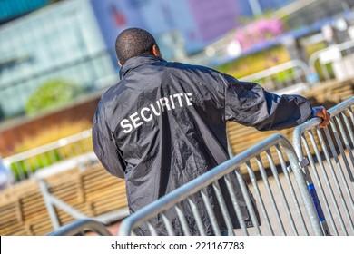 Agent de sécurité penché sur une clôture métallique et surveillant la zone de construction