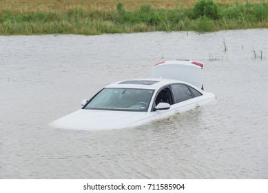 Sedan car swamped by flood water in East Houston, Texas, US by Harvey Tropical Storm. Submerged car on deep heavy high water road. Disaster Motor Vehicle Insurance Claim Themed. Severe weather concept